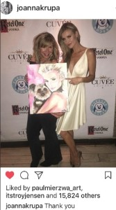 Artist Asta Razma presents Joanna Krupa with a portrait of herself and her rescue dog Rugby.